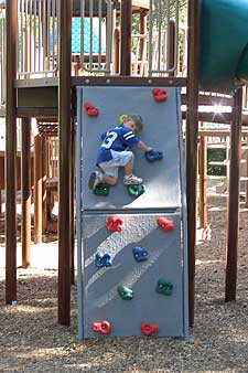 Child on playground climbing wall